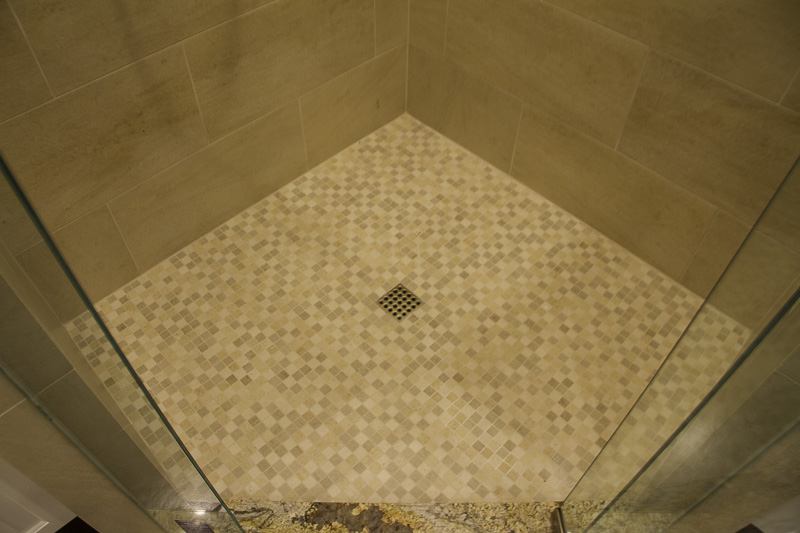 All the details are right with this shower floor, featuring 1x1 mosaic tiles and a square drain cover.
